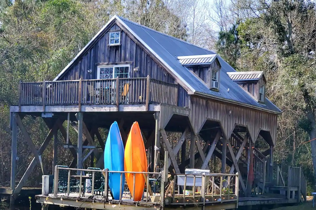 A cabin on stilts that overlooks the Louisiana Bayou that has its own dock with a grill, chairs, and kayaks