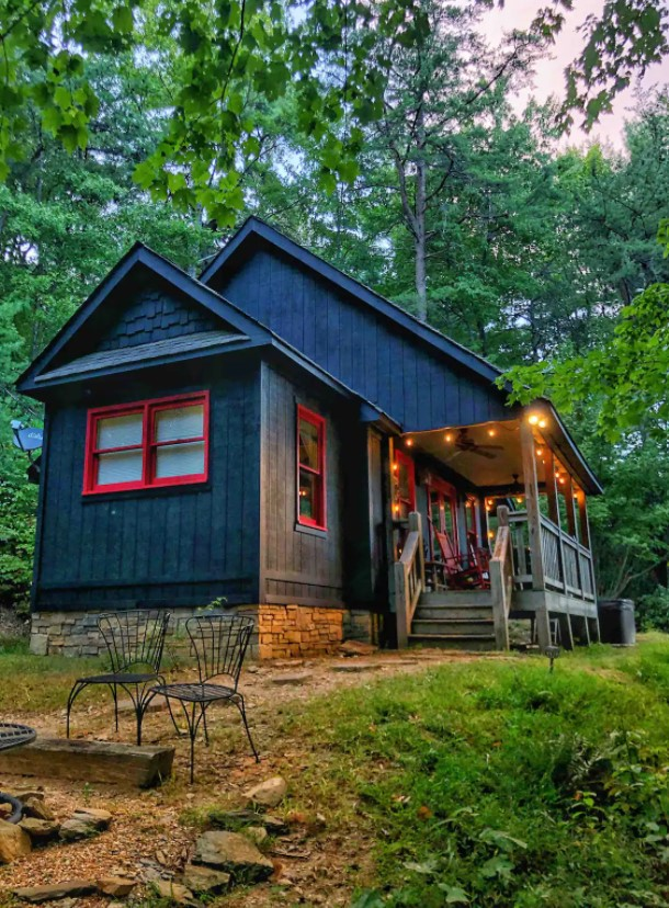 A black cabin with red trim surrounded by woods in Georgia