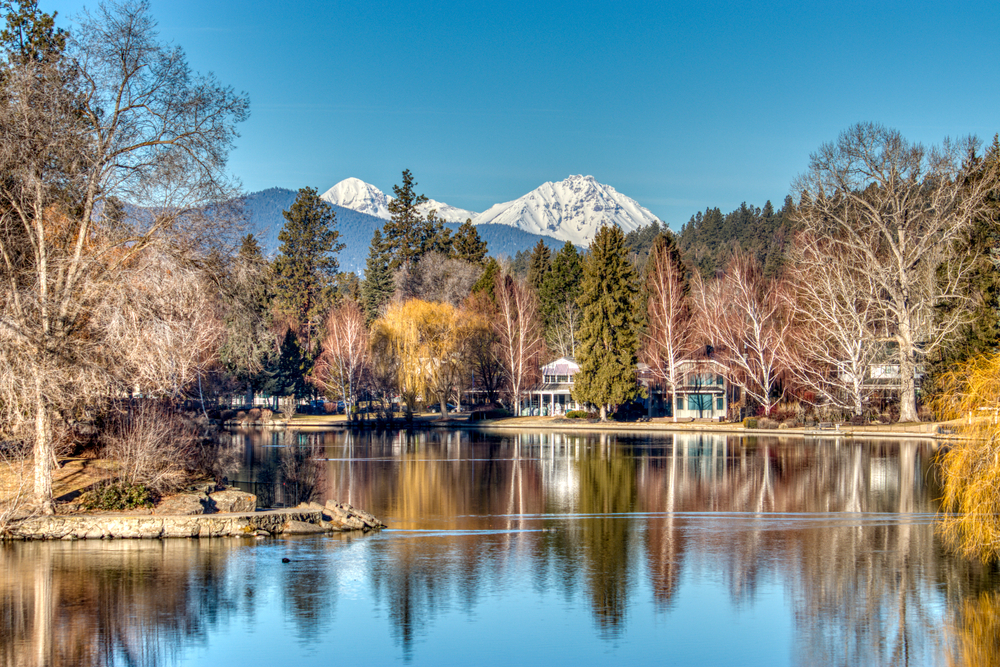 View of houses along the water with Mt. Rainier in the distance in Bend Oregon, one of the cutest small towns on the West Coast