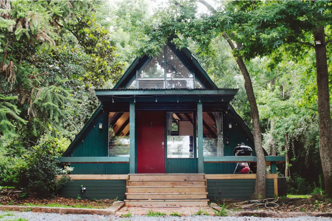 The front of a classic A-frame cabin that is painted teal with a dark red door with dense greenery behind it.