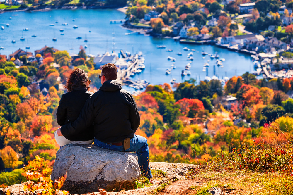 A couple sitting on a rock admiring Coastal Maine from on top of a hillside one of the best honeymoons in the usa