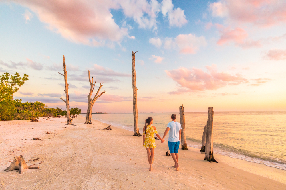 Couple walking on a beach in Florida as the sun sets