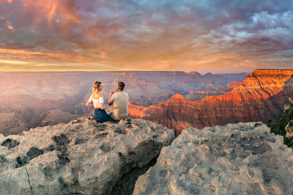 A couple sitting at the Grand Canyon during sunset