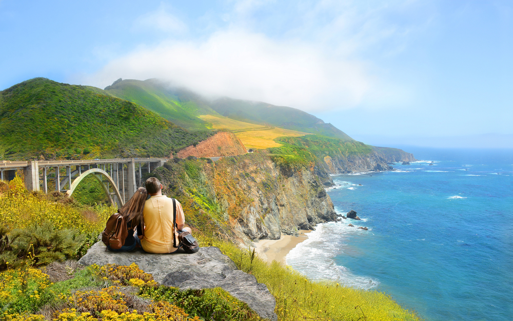 A couple sitting at the edge of a cliff looking out onto the pacific ocean and Big Sur