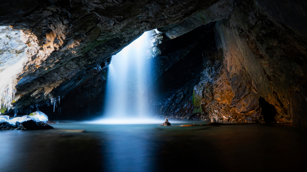 Looking at the Donut Falls as it drops into a cavern with a pool of water at the bottom