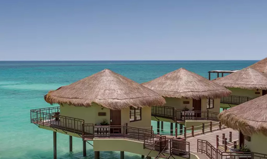 An overhead view of several overwater bungalows near the usa in mexico standing in clear blue water