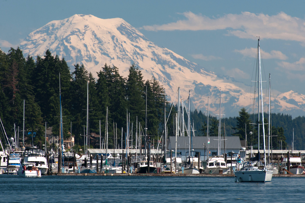 Sailing boats in Gig Harbor in the Puget Sound with mountain range in the distance