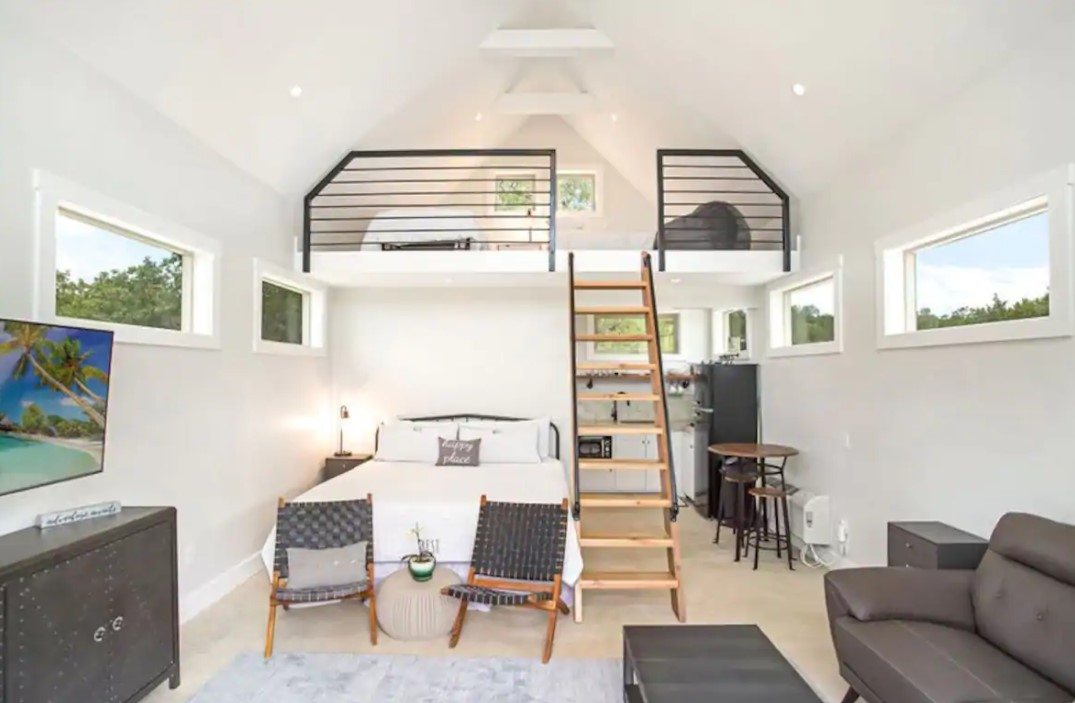 The inside of a modern studio style cabin painted bright white with black and natural wood accents
