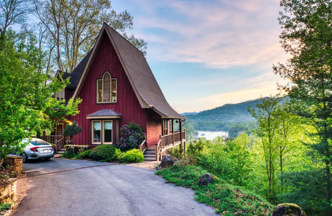 A large cabin with a tall A-frame roof with views of the lake and mountain range behind it.