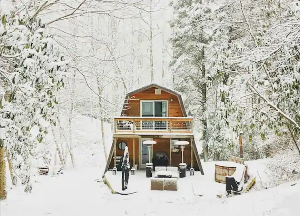 A charming cabin in the snow surrounded by woods in North Carolina one of the coziest cabins in the South