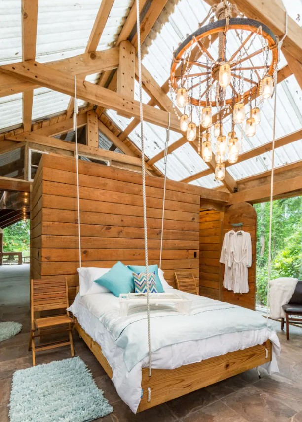 A suspended bed with a chandelier above it in a cabin full of windows in Texas