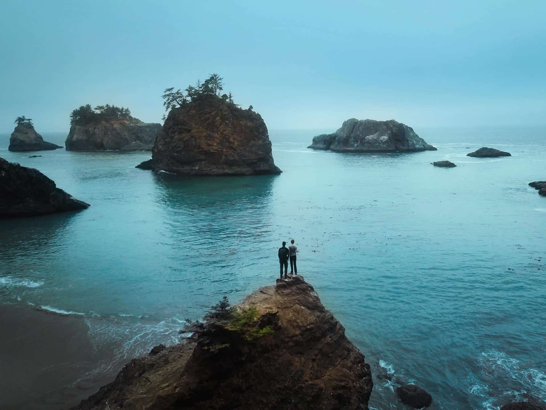 Couple standing on a rock at secret beach in Oregon one of the best honeymoons in the usa