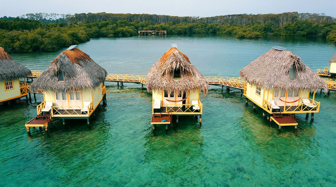 An arial view of several overwater bungalows in a line perched in crystal blue water in Panama