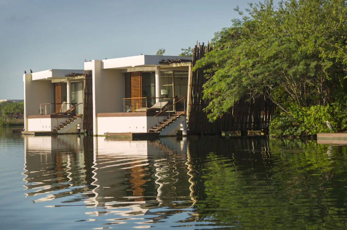 The otuside of two overwater bungalows near the usa that sit in a Mexico lagoon