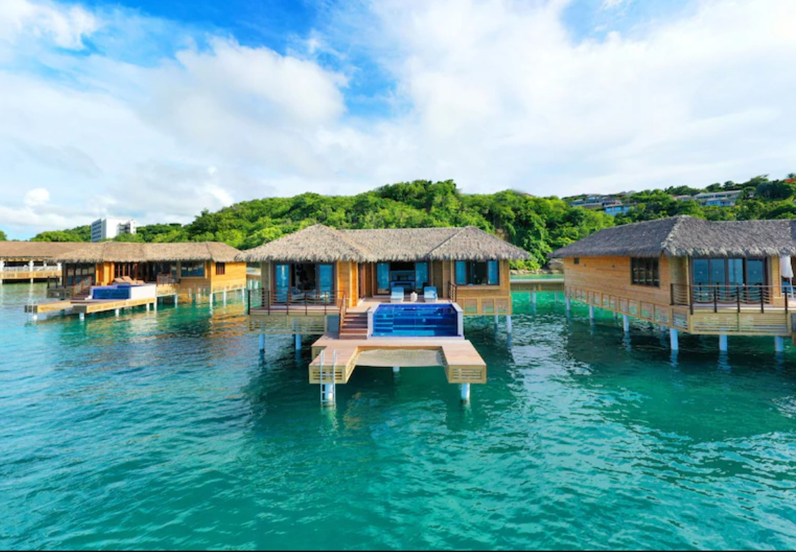 A view of several overwater bungalows in a line each with a private deck that has a plunge pool and a ladder that gives you direct access to the ocean