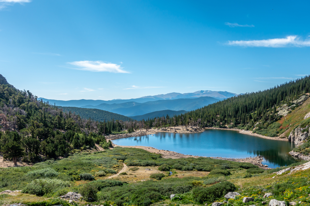 The lake at the bottom of Saint Mary's Glacier surrounded by tall pines and looking out onto mountain ranges