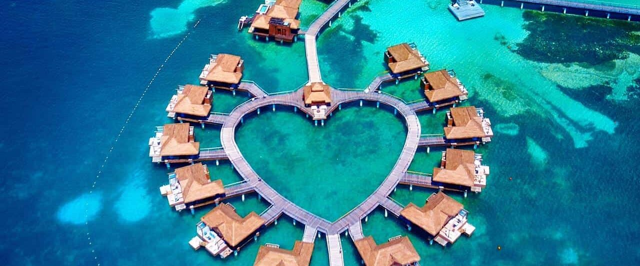 Arial shot of overwater bungalows near the usa in the shape of a heart