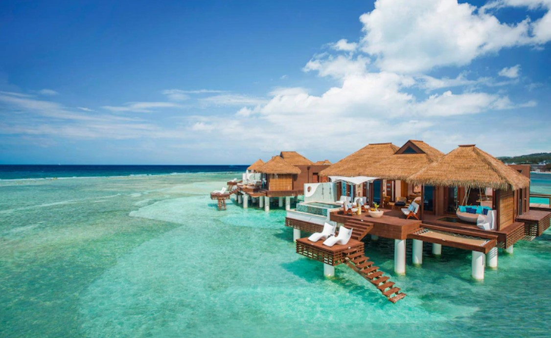 Several overwater bungalows near the usa looking out onto crystal blue ocean waters