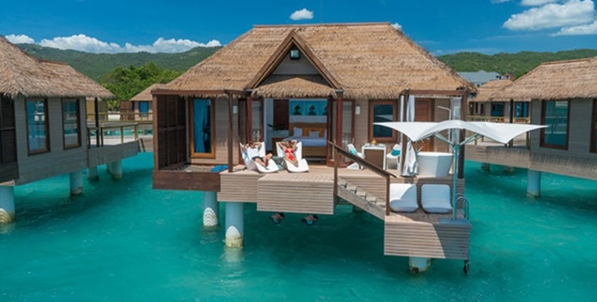 A couple sitting on the private deck of their luxury overwater bungalow at the Sandals Resort in Jamaica
