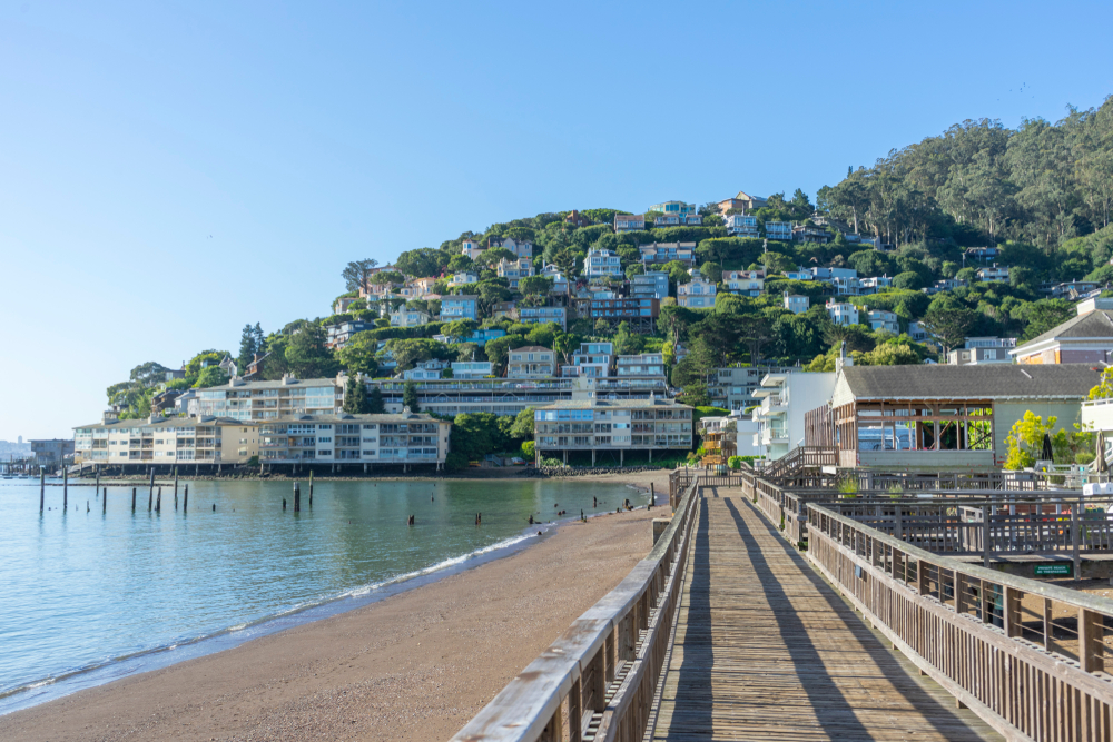 Looking down a narrow boardwalk next to the beach with the houses on a hill in the distance in Sausalito California