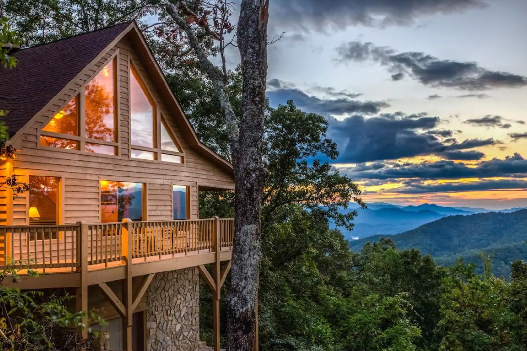 The front of a cabin set against a mountain side with views of the Great Smoky Mountains next to it