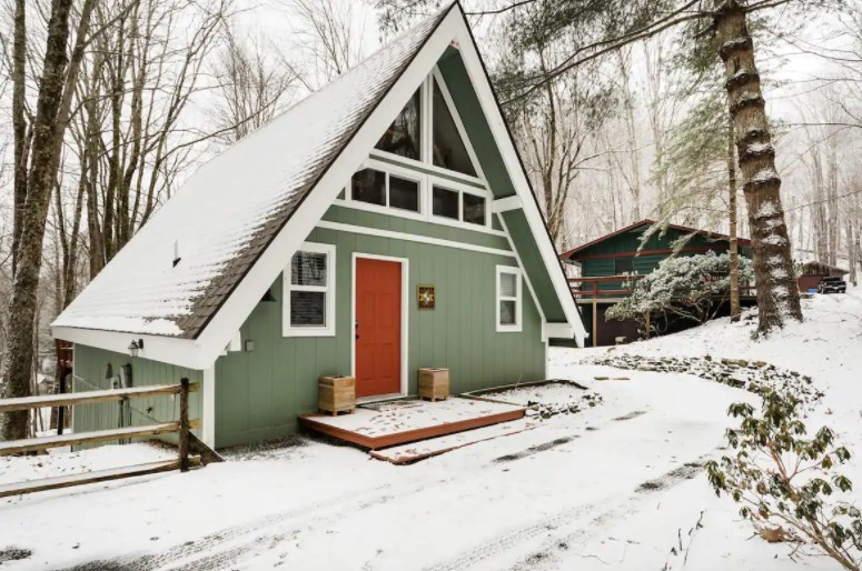 A cute A-frame cabin covered in snow in North Carolina one of the coziest cabins in the South