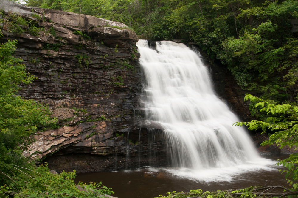 A very large waterfall coming off of a large rock formation surrounded by trees at Swallow Falls State Park
