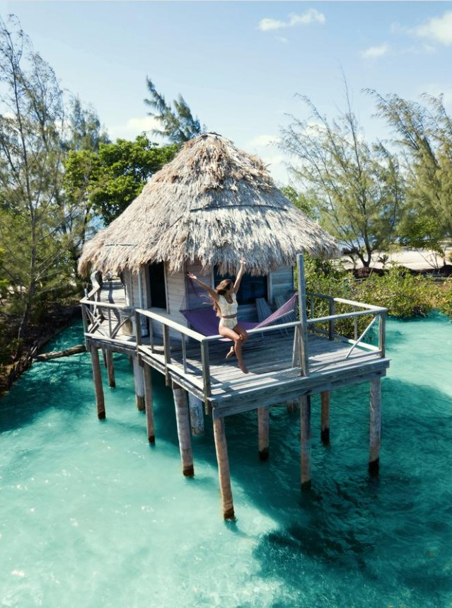 A woman sitting on the railing of a deck of a private overwater bungalow on a private island in Belize