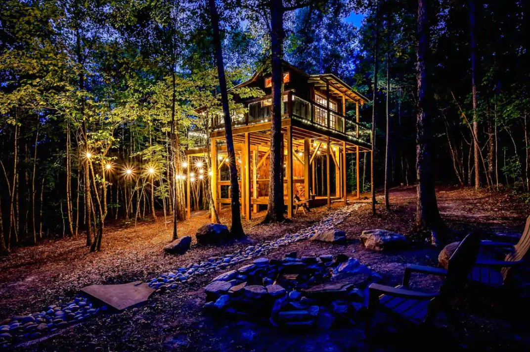 A cabin in the woods during twilight lit up by string lights in South Carolina one of the coziest cabins in the south