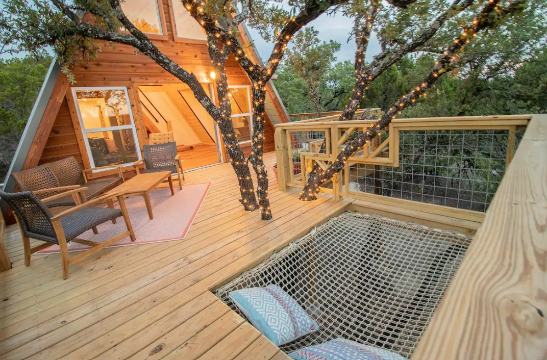 The front deck of a cabin in Texas that has a built in hammock that fits two people one of the coziest cabins in the South