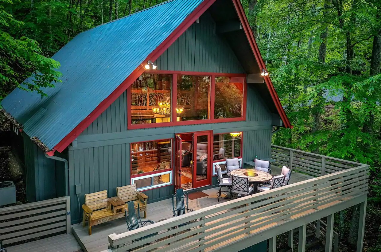 A slightly overhead view of the front of a large A-frame cabin with a large front porch surrounded by woods