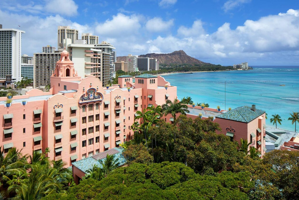 The pink Royal Hawai'ian Resort on the shores of Waikiki Beach with the Diamond Head Crater behind it one of the most romantic honeymoon destinations in the usa