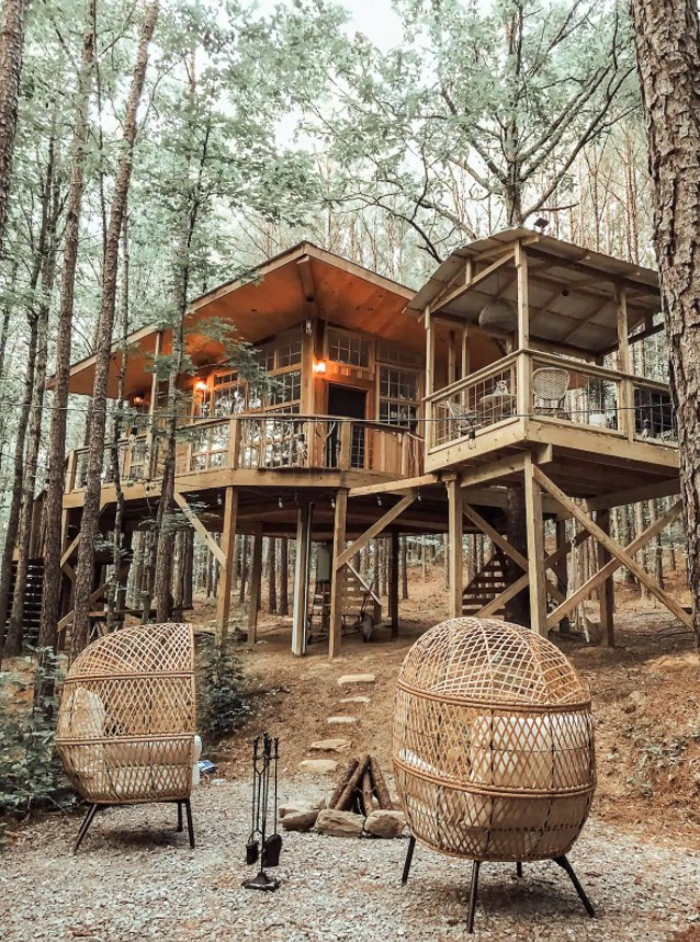 Looking up at a cabin from the firepit surrounded by trees in Alabama
