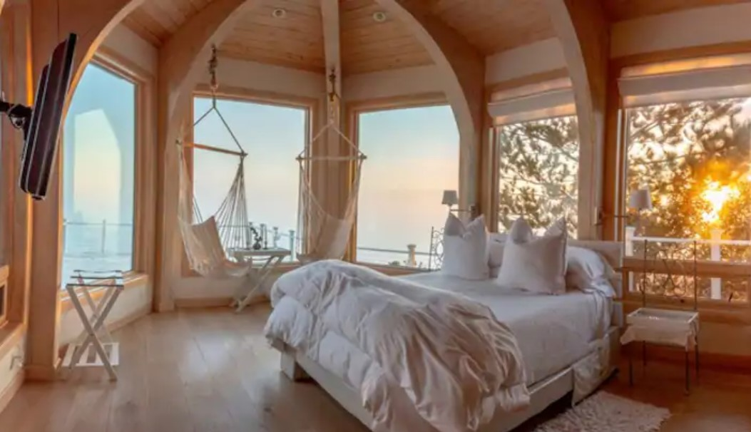 A queen-sized bed in a room full of windows that looks out to the ocean with two hammock seats inside