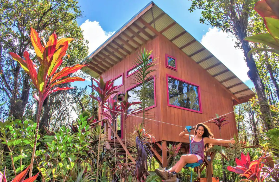 A woman using a small zip line outside of a tiny home treehouse surrounded by tropical plants one of the best airbnbs in Hawaii