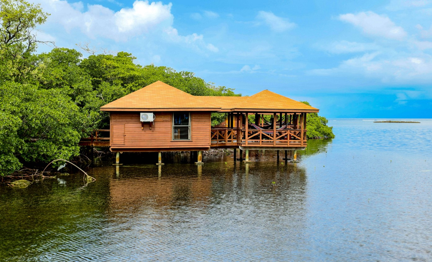 A tan overwater bungalow with a private covered deck with a hammock perched over the ocean in Honduras
