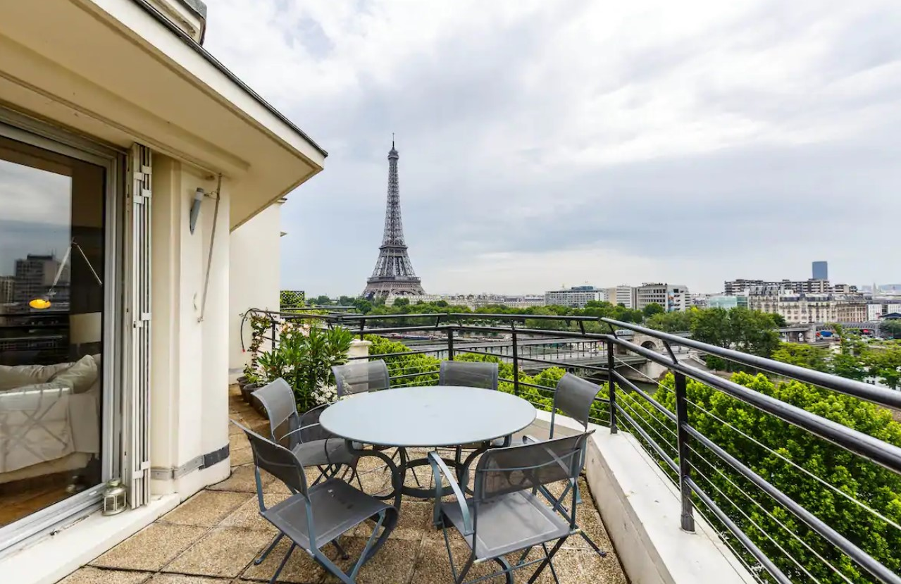 A large balcony with a glass table ad a view of the Eiffel Tower