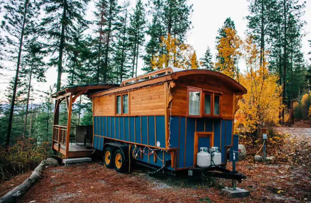 A blue and wood wagon tiny home surrounded by trees with a large deck on the back in Leavenworth Washington best Airbnbs in Washington