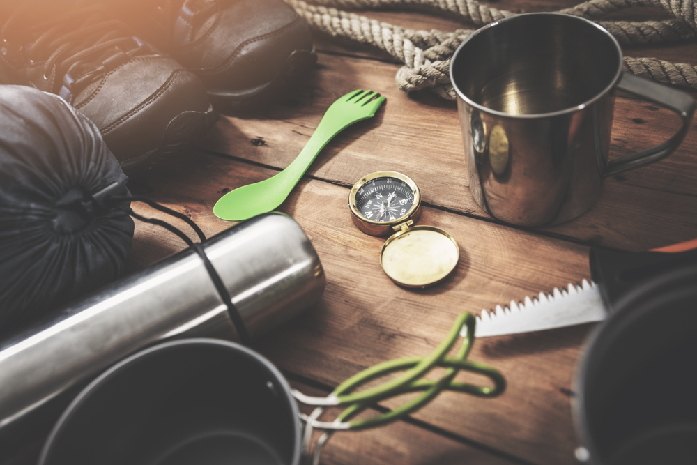 photo of a spork, hiking boots, and a compass, all important car camping essentials