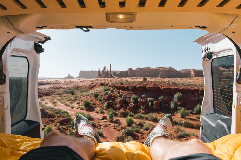photo of a desert view from the back of a van showcasing socks, one of the important car camping essentials