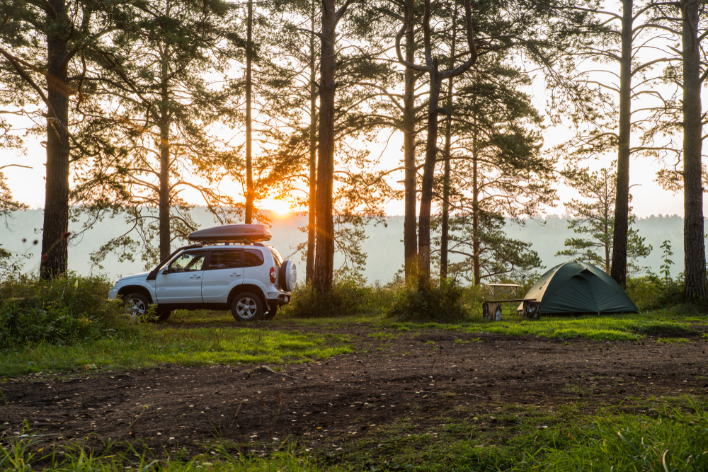 photo of a car and tent at sunset