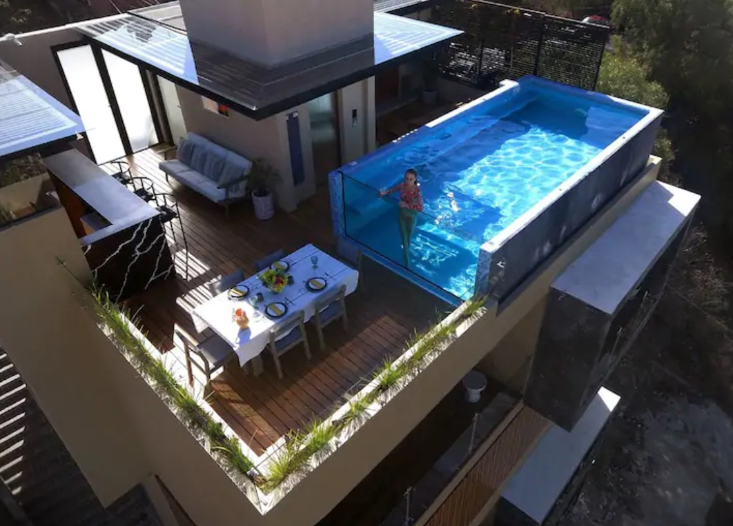 An aerial view of a rooftop infinity pool and common area airbnbs in mexico