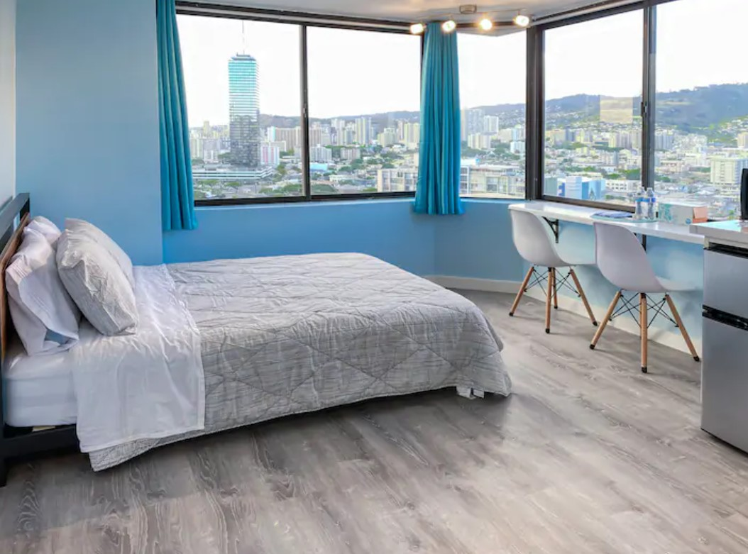 The interior of a high rise studio apartment painted blue with 180 degree views of the Honolulu skyline best airbnbs in Hawaii