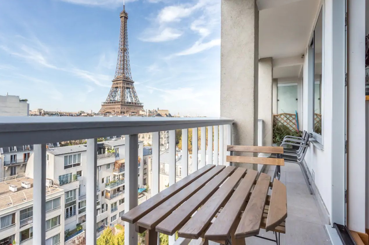 The view of the Eiffel Tower on a small private balcony in a studio apartment in Paris
