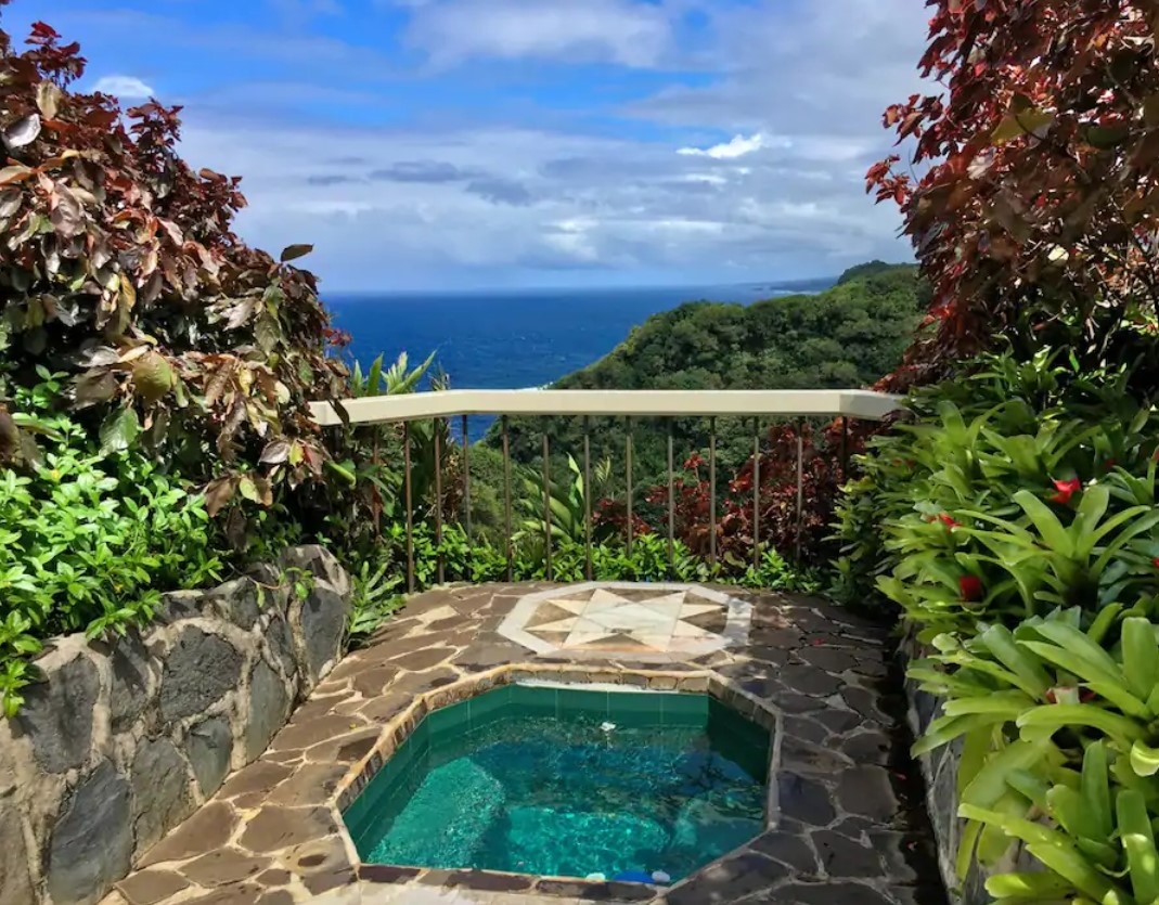 An emerald tiled hot tub surrounded by a natural stone patio with a railing that looks out onto a cliff with views of the pacific ocean