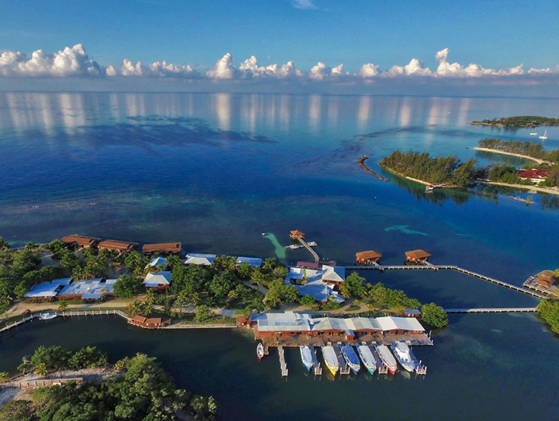An aerial image of the CoCo View Resort in Honduras with four overwater bungalows in the Caribbean and several ocean front bungalows
