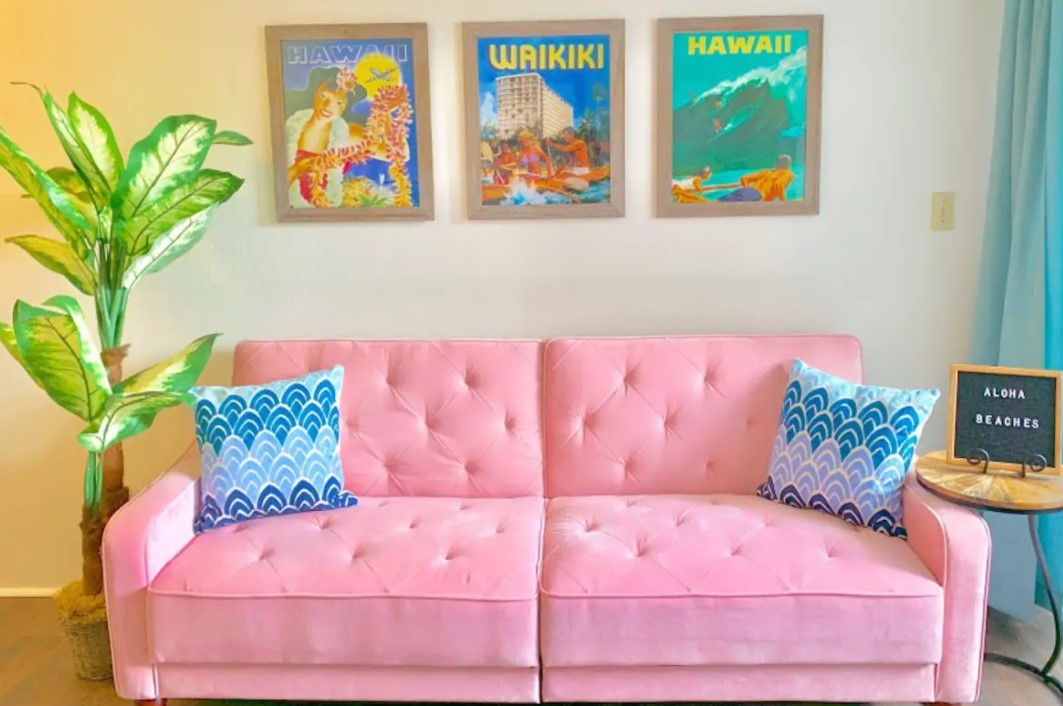 A pastel pink velvet sofa surrounded by bright Hawaiian travel posters best airbnbs in Hawaii