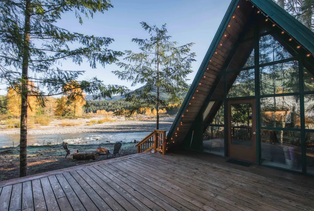 An A-frame cabin with a large front deck on the banks of the Cowlitz River in Washington