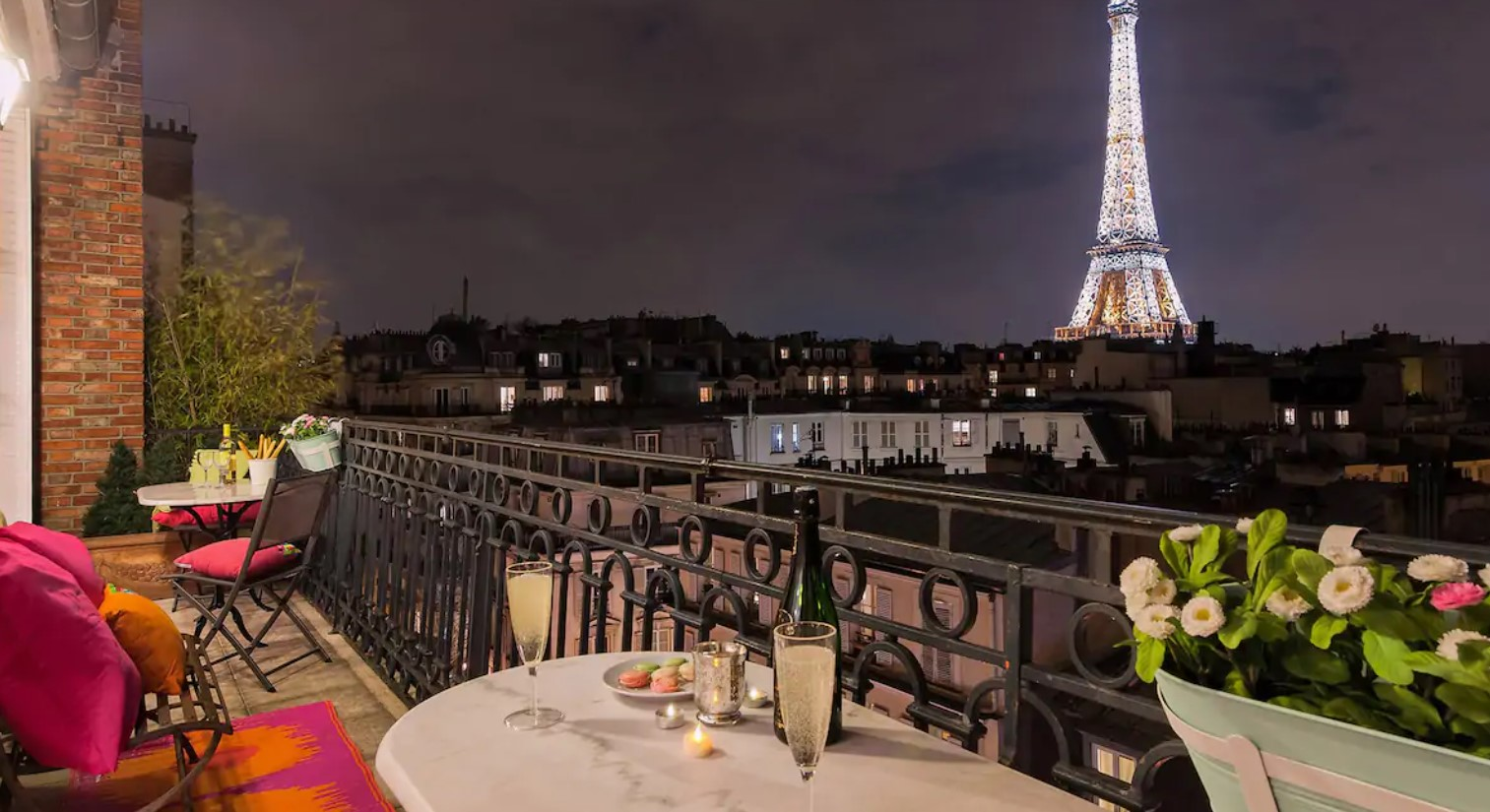 The view of the Eiffel Tower lit up at night from a large private terrace in an apartment in Paris