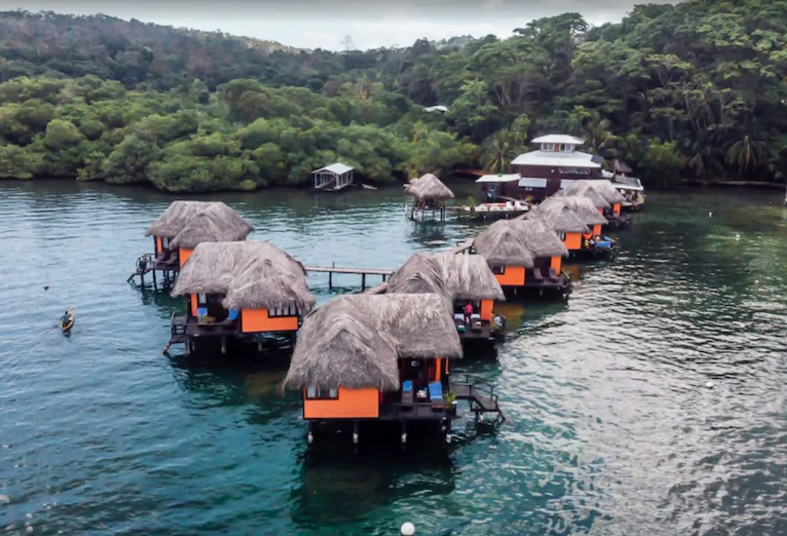 An aerial view of seven bright orange overwater bungalows with natural thatch rooves in the Caribbean